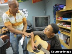 MusicianCorps' David Meletiche works with Rajahn Blevins in his after-school guitar class. (Courtesy MusicianCorps)