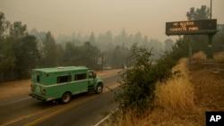 """2018年7月16日一辆消防运输车在140号高速公路上的加利福尼亚州马里波萨优胜美地国家公园入口处。电子标牌提示:""""优胜美地公园入口关闭。"""""""