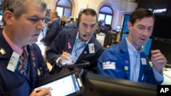 John McNierney, right, trading GE stock for Citadel Securities, updates John Panin, left, and Greg Rowe, center, with the stock's price at the New York Stock Exchange, July 22, 2016.