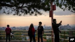 Varias personas con máscaras para protegerse del nuevo coronavirus observan el panorama desde un mirador en el tope de una colina en un parque público de Beijing, el sábado 25 de abril de 2020.