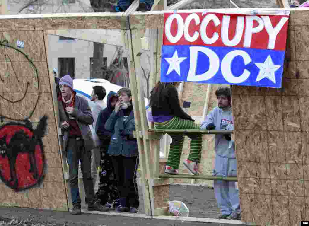 Occupy DC protesters stand inside a structure set up overnight in McPherson Square, Sunday, Dec. 4, 2011 in Washington. Protesters are refusing to dismantle the unfinished wooden structure erected in the park. (AP Photo/Manuel Balce Ceneta)
