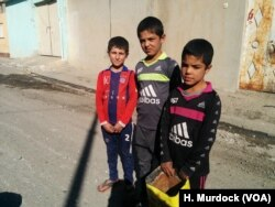 """We are scared, but we are used to it a little,"" says Fahel, 12, (L) on his way to find food for his family's cow despite the ongoing gunfire and mortars on Nov. 19, 2016 in Mosul, Iraq."