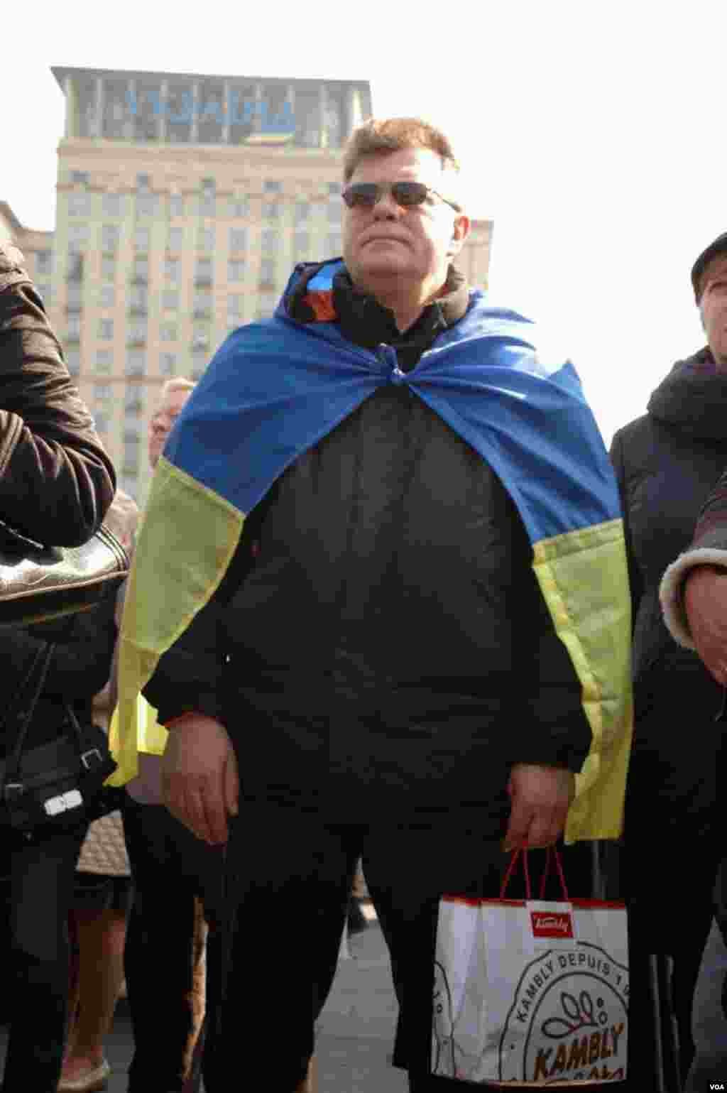 A man wearing a Ukranian flag listens to speakers at a unity rally in Maidan, central Kyiv. (Steve Herman/VOA)