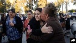 Một phụ nữ ôm hôn em gái, người sống sót trong vụ xả súng giết chết 14 người, trong đó có cô Tín Nguyễn, ở San Bernardino, ngày 2/12/2015.