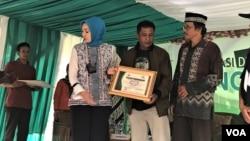 Ketua Bank Mata Jawa Barat Alma Lusiyati (kiri) memberikan penghargaan kepada perwakilan warga Tenjowaringin, kabupaten Tasikmalaya, yang menjadi donor mata dalam deklarasi desa siaga donor mata di desa tersebut, Sabtu (30/12/2018). (Foto: VOA/Rio Tuasikal)