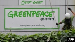 "FILE - Activists of Greenpeace rappell down their office building where they are head quartered to unfurl banners ""democracy"" and ""freespeech"" in Bangalore, May 15, 2015."