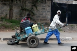 FILE - A water vendor with containers on his wheel cart attempts to deliver water in Nairobi, Kenya, July 10, 2009.