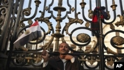 An anti-government protester gestures as he sits outside the Egyptian Parliament in Cairo, Egypt, Feb 9, 2011