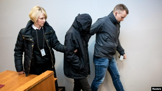 Finnish police officers bring one of the two Iraqi men, who were detained on suspicion of participating in killings that were filmed by Islamic State, to a custody hearing at the Tampere District Court in Tampere, Finland, Dec. 11, 2015.