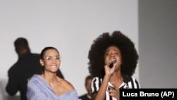 Designer Stella Jean joins the band Soul Voices at the end of her fashion show in Milan, Italy, Sunday, September 24, 2017. (AP Photo/Luca Bruno)