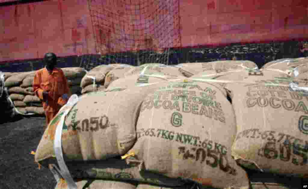 A worker stands among sacks of cocoa beans as they are loaded for shipment at the port in Abidjan, Ivory Coast, May 10, 2011.
