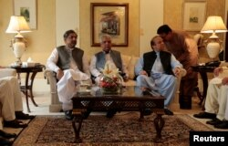 FILE - Former Pakistani Prime Minister Nawaz Sharif speaks with an official as he sits with KPK Governor Iqbal Zafar Jhagraand current Prime Minister Shahid Khaqan Abbasi (L) during a meeting before leaving Punjab house in Islamabad, Pakistan, Aug. 9, 2017.