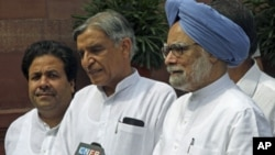 India's Prime Minister Manmohan Singh (R) speaks to the media as Minister of State for Parliamentary Affairs Rajiv Shukla (L) and Parliamentary Affairs Minister Pawan Kumar Bansal watch on the opening day of the monsoon session of the Indian Parliament in