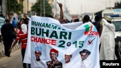 All Progressives Congress (APC) supporters hold a banner with a photograph of former military ruler Muhammadu Buhari in Lagos, Nigeria, Dec. 10, 2014.