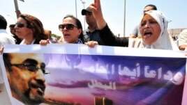 Protesters hold a picture of slain political activist Abdelsalam al-Mosmary during his funeral in Benghazi July 27.
