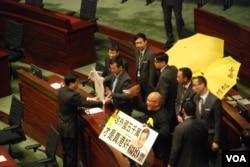泛民主派立法会议员陈伟业(右)及陈志全在议会内,举起讽刺梁振英的标语,被保安人员抬离会场(美国之音汤惠芸拍摄)