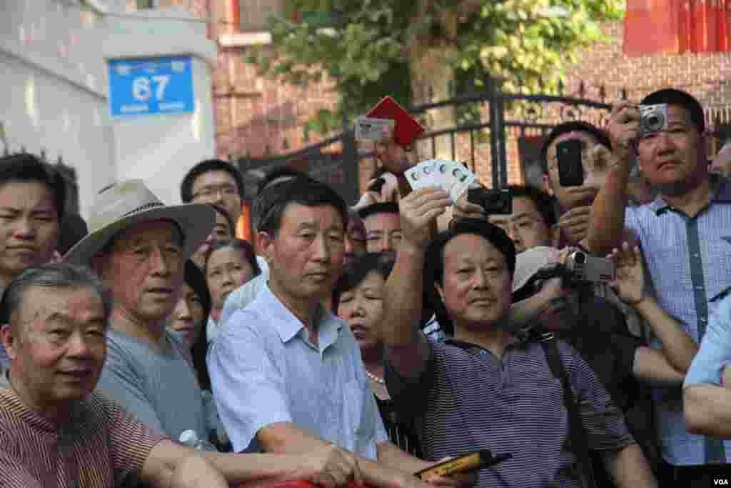 看到我戴着美国之音的记者证,有民众高举手中的中华人民共和国身份证,说希望能够被允许进入警戒区
