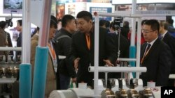 An exhibitor, center, talks to a visitor about his company's machine at the China Coal & Mining Expo in Beijing, Oct. 30, 2015. World Bank experts say economic growth will slow further in China this year.