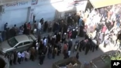 This image from amateur video made available by Shaam News Network purports to show people gathered in Homs, Syria, February 12, 2012.