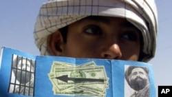 ایک افغان شہری اتحادی افواج کی طرف سے تقسیم کیا ہوا پمفلٹ دکھارہا ہے جو کہ ملا عمر کی گرفتاری پر انعام کے اعلان سے متعلق ہے۔