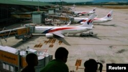FILE - Children look at Malaysia Airlines Boeing 737-800 aircrafts parked at Kuala Lumpur International Airport.