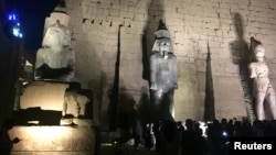 Tourists and Egyptians look at a huge granite statue of Ramses II,, center, after the completion of the restoration work, hours after the Egyptian Ministry of Antiquities revealed the contents of a Pharaonic cemetery on the western bank in Luxor, south of