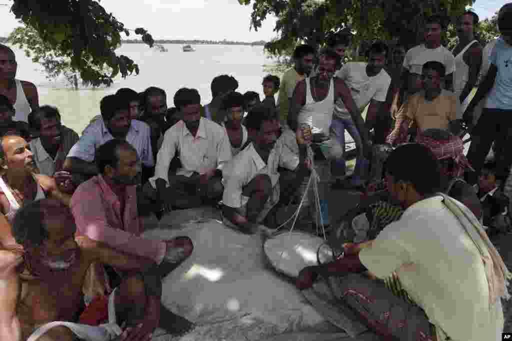 Dân làng bị ảnh hưởng bởi lũ lụt nhận gạo cứu trợ được chính phủ phân phối tại làng Gagalmari, bang Assam, ngày 2 tháng 7 năm 2012