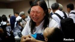 Seorang perempuan, yang suaminya menjadi korban kecelakaan pesawat Lion Air JT610, menangis sambil menggendong anaknya setelah konferensi pers mengenai proses pencarian pesawat di sebuah hotel di Jakarta, Senin, 5 November 2018. (Foto: Reuters)