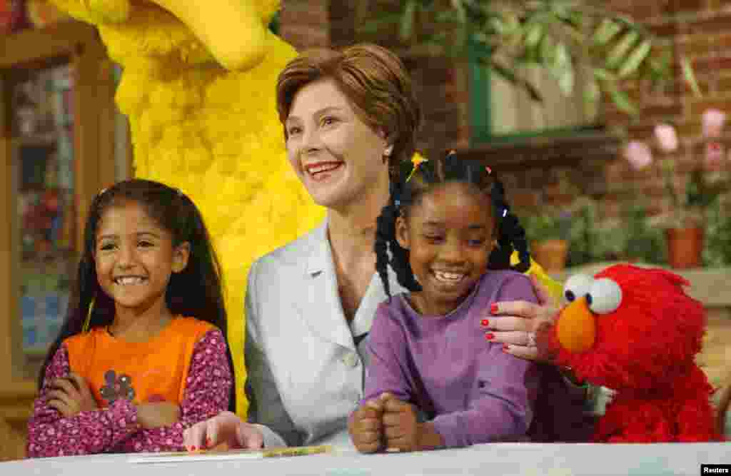 U.S. first Lady Laura Bush (center) poses with Sydney Martinez (left) Sienna Jefferies (right) and Sesame Street character, Elmo, after reading a book to the children, New York, Sept. 19, 2002.