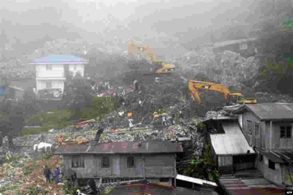 Rescuers and volunteers try to clear piles of garbage under thick fog in Baguio City, northern Philippines on Monday Aug. 29, 2011. Several tons of garbage buried some shanties after a dumpsite's concrete wall collapsed due to strong winds and rain brough