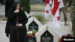 Seorang perempuan meratapi kuburan seorang prajurit Georgia yang tewas saat konflik antara Georgia dan Rusia di Ossetia selatan pada tahun 2008. (Foto: dok.)
