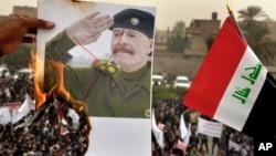 Un manifestante prende fuego a un poster de Izzat Ibrahim al-Douri, el oficial de más alto rango del régimen de Saddam Hussein que no fue nunca capturado tras la caída del régimen.
