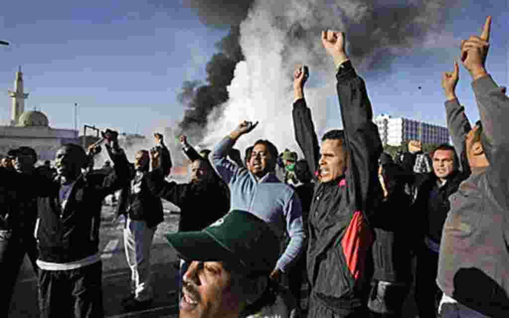 Manifestantes en respaldo a Gadhafi delante de una explosión de un tanque de crudo.
