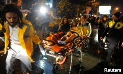 FILE - An injured woman is carried to an ambulance from a nightclub where a terrorist attack took place during a New Year's party in Istanbul, Turkey, Jan. 1, 2017.