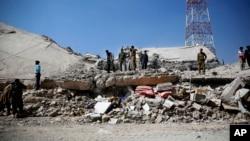 Polisi memeriksa reruntuhan markas polisi di Sana'a, Yaman yang hancur akibat serangan udara koalisi, Senin (18/1).