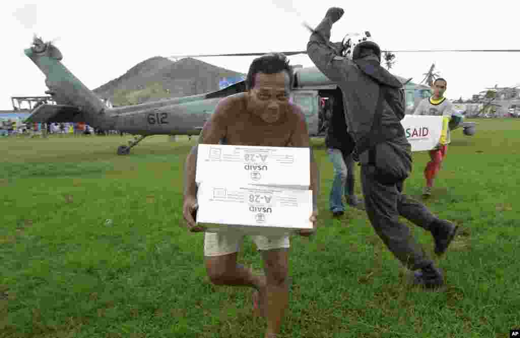 A Philippine man carries aid from a U.S. Navy Seahawk helicopter in Palo, Philippines, Nov. 20, 2013.