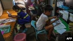 Coleen Giselle Ahilon (kiri) dan Churt Iverson Steven Ordones (kanan) memulai sekolah dari rumah dengan menggunakan ponsel dan modul pembelajaran yang sudah dicetak, di pinggiran kota kota Mandaluyong, Manila, 5 Oktober 2020. (Foto: Maria Tan / AFP)