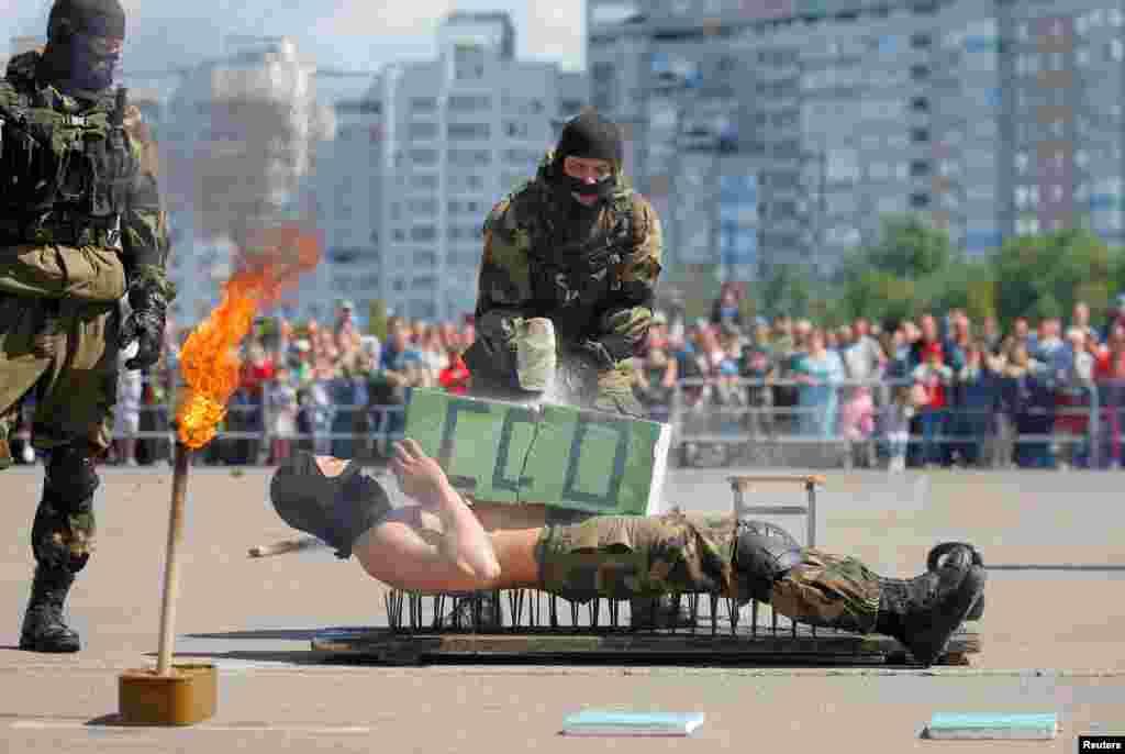 Pasukan penerjun payung Belarusia menunjukkan kemampuan fisik mereka dalam perayaan memperingati HUT ke-90 berdirinya pasukan udara negara itu di kota Minsk, Belarusia.