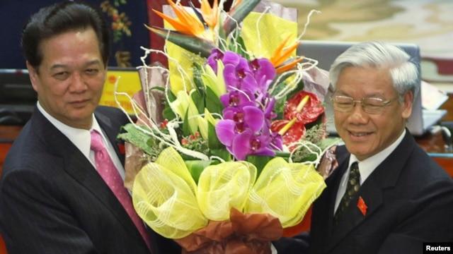 Thủ tướng Việt Nam Nguyễn Tấn Dũng nhận hoa từ tay Tổng Bí thư Nguyễn Phú Trọng sau khi ông Dũng tái đắc cử thủ tướng ngày 26 tháng 7, 2011 tại Hà Nội.