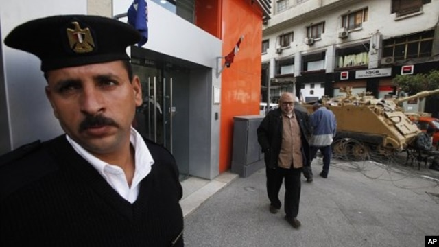 An Egyptian policeman stands guard outside a bank in Cairo February 20, 2011