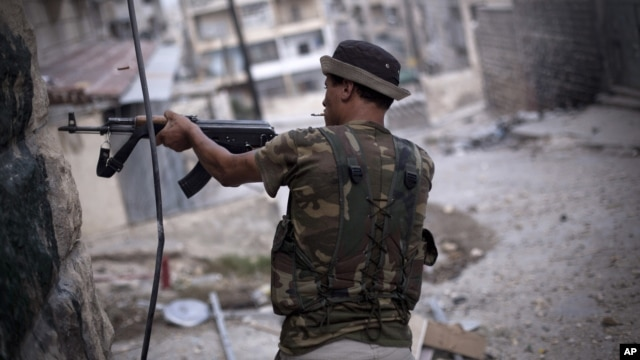 A Free Syrian Army fighter fires his weapon at Syrian Army positions in Aleppo, Syria, September 11, 2012.