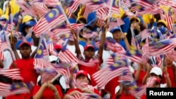 Young Malaysians wave flags during rehearsals for National Day celebrations, marking the anniversary of the country's independence, at the Independence Square in Kuala Lumpur, in this August 29, 2012 file photo.
