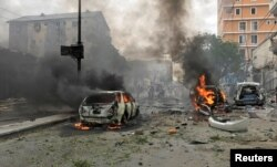 FILE - Vehicles burn at the scene of an explosion in Mogadishu, Somalia, July 30, 2017.