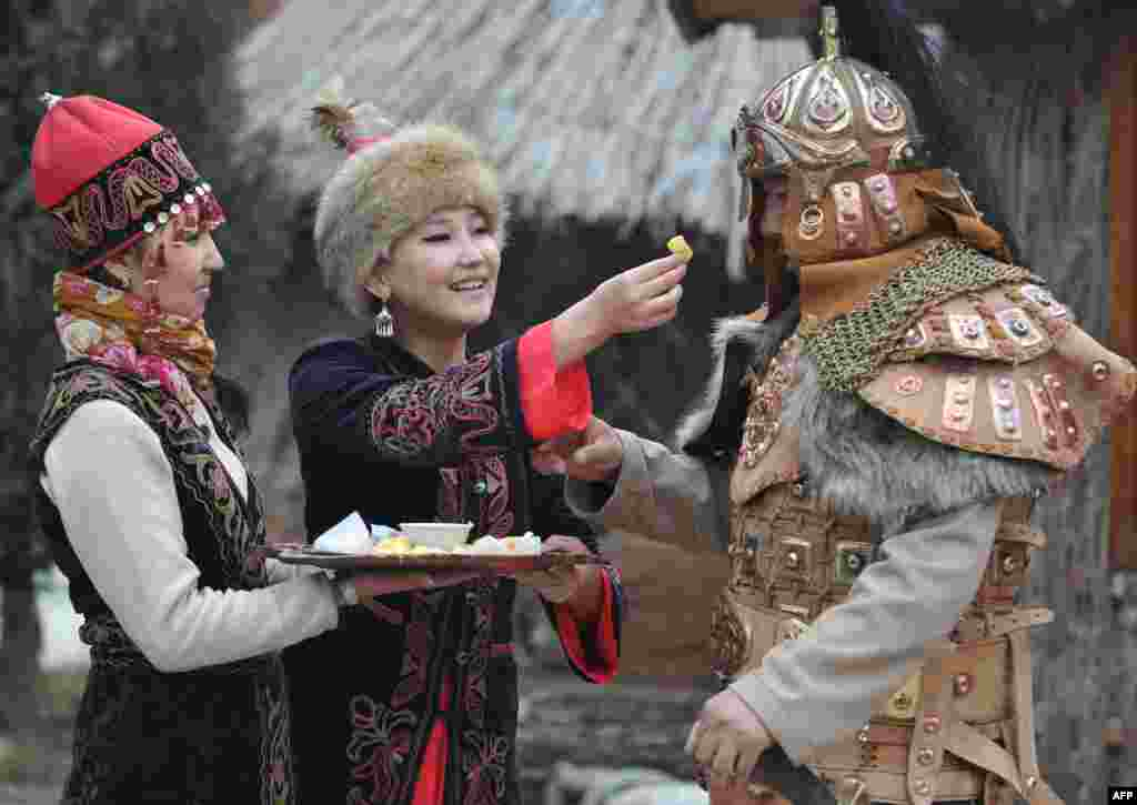 """Những người phụ nữ và người đàn ông trong trang phục truyền thống của Kyrgyzstan đón mừng Nowruz (năm mới) ở ngoại ô thủ đô Bishkek của Kyrgyzstan. Nowruz, tiếng Farsi nghĩa là """"Năm mới,"""" là một lễ hội cổ xưa đánh dấu ngày đầu tiên của mùa xuân ở Trung Á."""