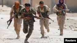 무장한 시리아 쿠르드족 인민수비대(YPG)가 지난 7월 시리아 락까 거리를 가로질르며 달리고 있다.