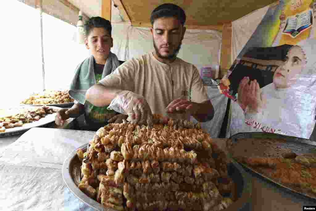 A Syrian refugee displays sweets for sale during the month of Ramadan at Al Zaatri refugee camp in the Jordanian city of Mafraq, near the border with Syria, July 30, 2013.