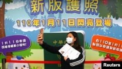 一名台北婦女在台灣新版護照發布廣告前自拍留念。(2021年1月11日)