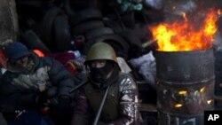 Un manifestante junto a un barril en llamas en una barricada cerca de la Plaza de Independencia en Kiev.