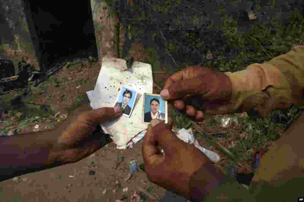 Men show passport pictures they found at the site of a bomb blast, Peshawar, Pakistan, Sept. 27, 2013.