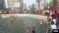 Des enfants jouent dans une fontaine publique en raison de la canicule au Caire, en Egypte, le 6 juillet 2016. (H. Elrasam / VOA)